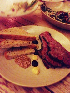 Grainy shot of grain mustard and brisket.